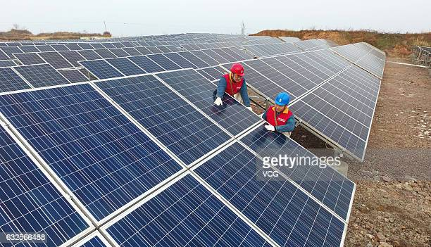 Workers check the gridconnected photovoltaic system built on an abandoned mine at Chihe Town on January 23 2017 in Chuzhou Anhui Province of China...