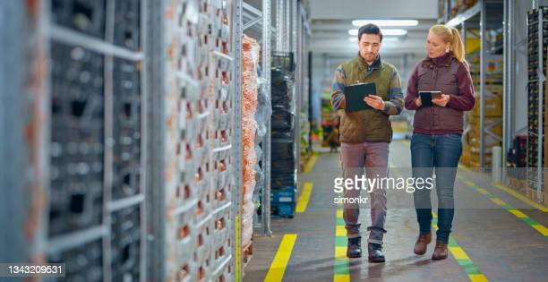 workers checking shipment in warehouse - coat stock pictures, royalty-free photos & images