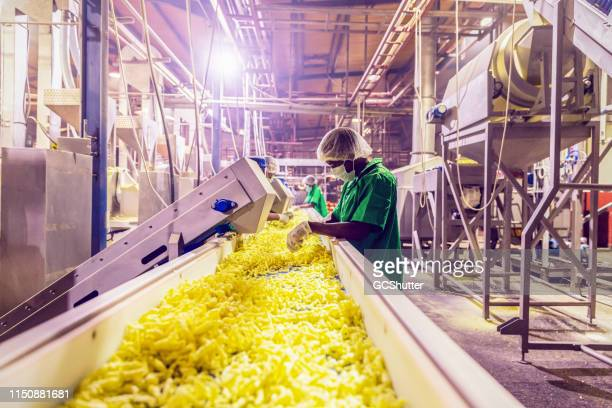Workers Checking the Quality of Freshly Prepared Snacks at a Factory in Africa