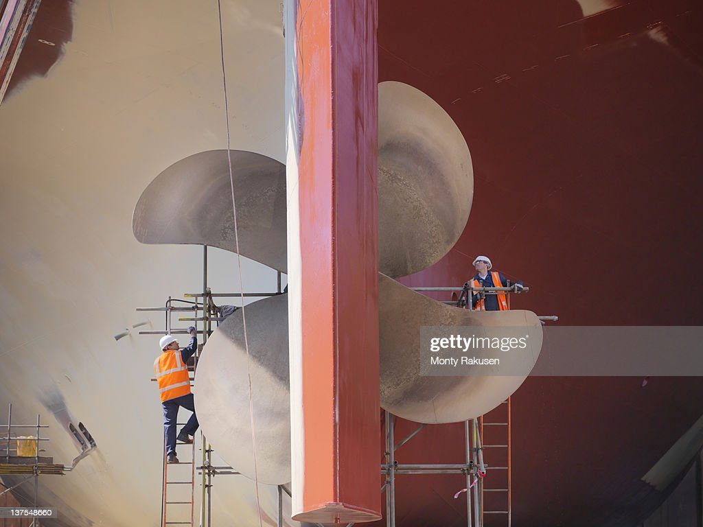 Workers checking underside of ship in dry dock : Stock Photo