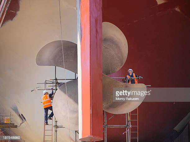 workers checking underside of ship in dry dock - watervaartuig stockfoto's en -beelden