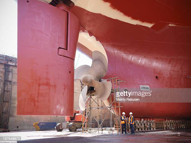 Workers checking underside of ship in dry dock