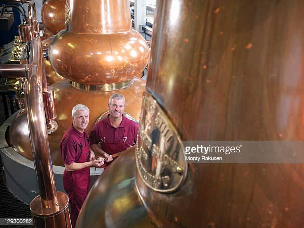 Workers checking whisky stills in distillery