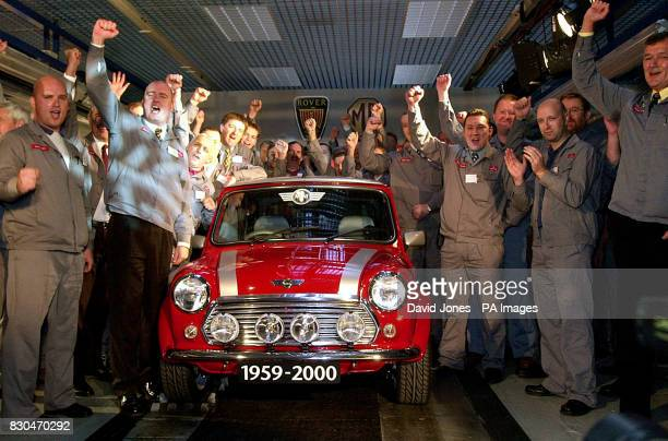 Workers cheering as the 5862nd and final classic Mini rolls off the production line at the MG Rover Group factory in Longbridge Birmingham After 41...