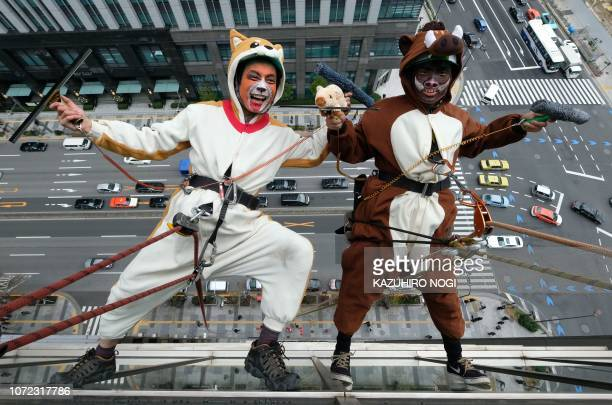 TOPSHOT Workers clad in a dog and a wild boar costumes to represent the outgoing year of the dog and incoming year of the wild boar clean windows on...