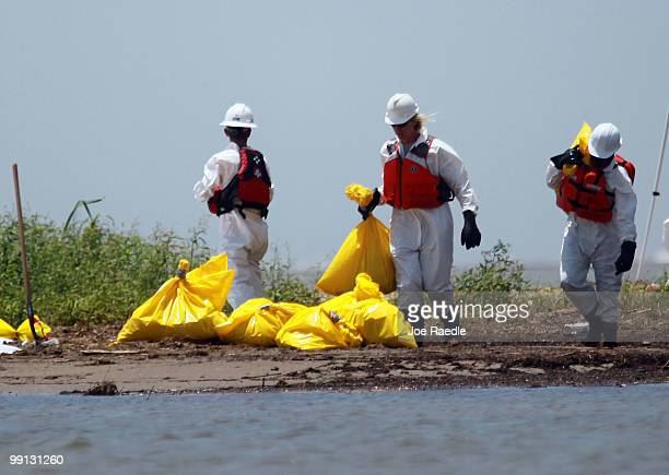 Workers clean a beach after tar balls washed up as efforts continue to contain BP's massive oil spill on May 12 2010 in South Pass Louisiana The...