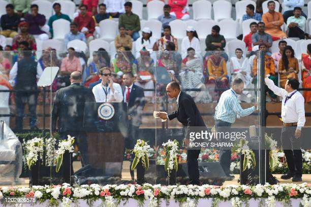 Workers clean a bulletproof glassenclosure around the podium before 'Namaste Trump Rally' ahead of the arrival of US President Donald Trump and...