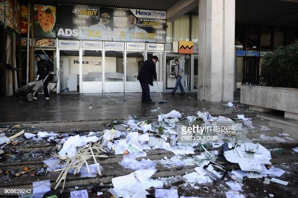 Workers clean a train station dammaged overnight on January 15 2011 in Tunis There were scenes of looting overnight in the suburbs of Tunis witnesses...