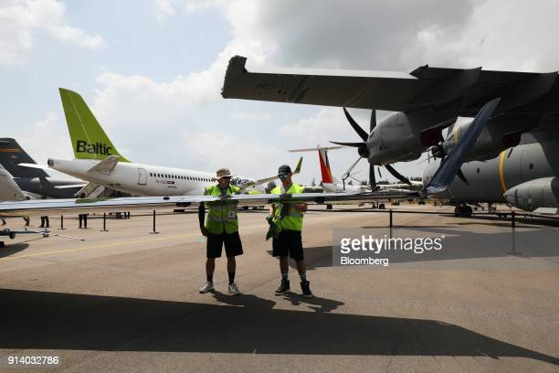 Workers clean an Embraer SA Phenom 300 aircraft on display during a media preview day at the Singapore Airshow held at the Changi Exhibition Centre...