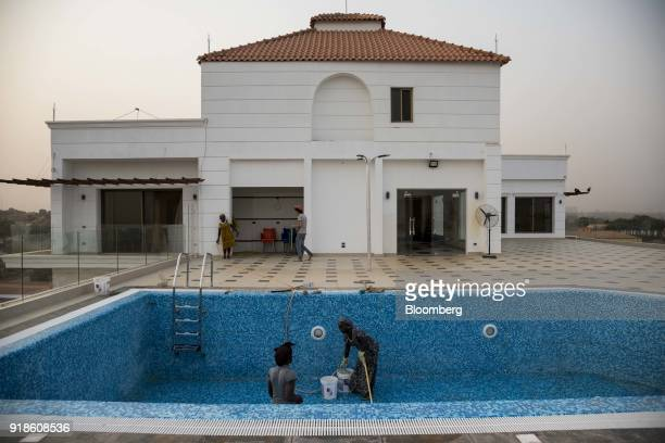 Workers clean an empty swimming pool at the underconstruction Bissau Royal Hotel in Bissau GuineaBissau on Tuesday Feb 13 2018 The International...