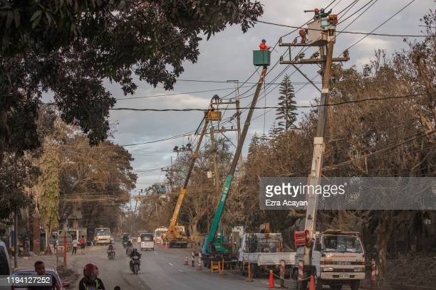 Workers clean electrical posts covered in volcanic ash from Taal Volcano's eruption on January 17 2020 in Tagaytay city Cavite province Philippines...