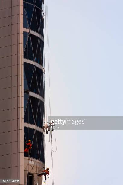 workers clean exterior glass of a skyscraper