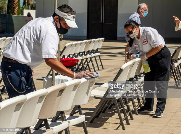 Workers clean folding chairs following a morning outdoor mass at Christ Cathedral in Garden Grove on Sunday, July 19, 2020. Services at Christ...