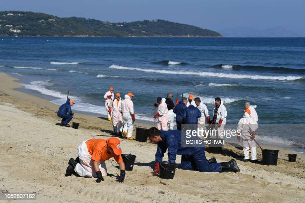 Workers clean hydrocarbon slabs from oil spill from two ships that collided off the waters of Corsica on the beach in Ramatuelle in the Gulf of...