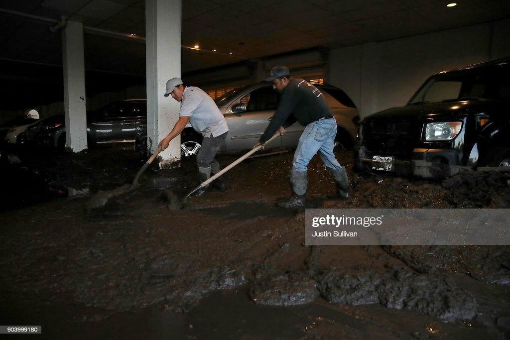 Workers clean mud from the parking garage at the Montecito Inn on January 11, 2018 in Montecito, California. 17 people have died and hundreds of homes have been destroyed or damaged after massive mudslides crashed through Montecito, California early Tuesday morning.