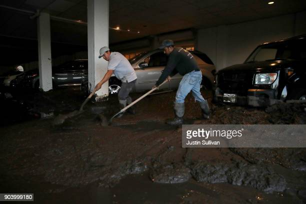 Workers clean mud from the parking garage at the Montecito Inn on January 11 2018 in Montecito California 17 people have died and hundreds of homes...