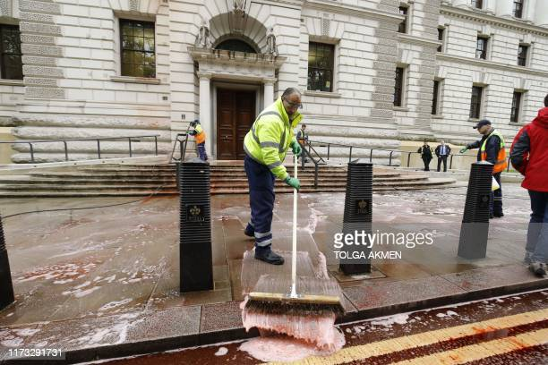 Workers clean outside the Treasury building in central London on October 3 2019 after protesters from climate group Extinction Rebellion sprayed fake...