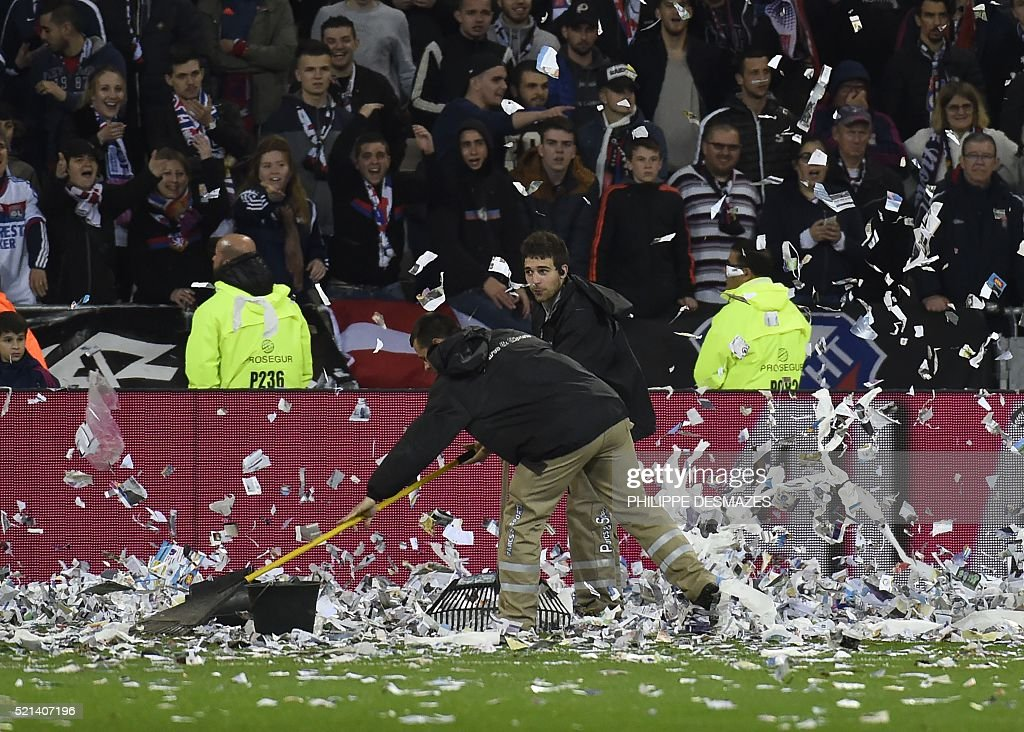 Workers clean papers thrown on the field by fans during the French L1 football match Olympique Lyonnais and OGC Nice on April 15, 2016, at the New Stadium in Decines-Charpieu near Lyon, southeastern France.