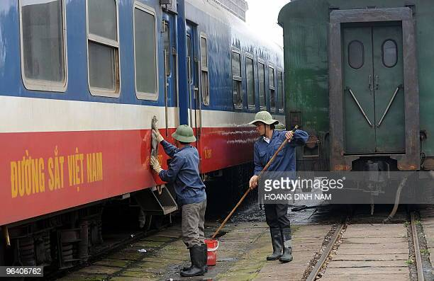 Workers clean passenger wagons at a train station in Hanoi on January 27 2010 The trains were imported by the French in the late 19th century and are...