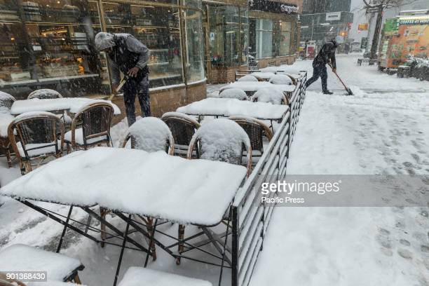 Workers clean sidewalk with cafe tables covered with snow in Manhattan under heavy snow storm cold and wind A giant winter bomb cyclone hit the US...