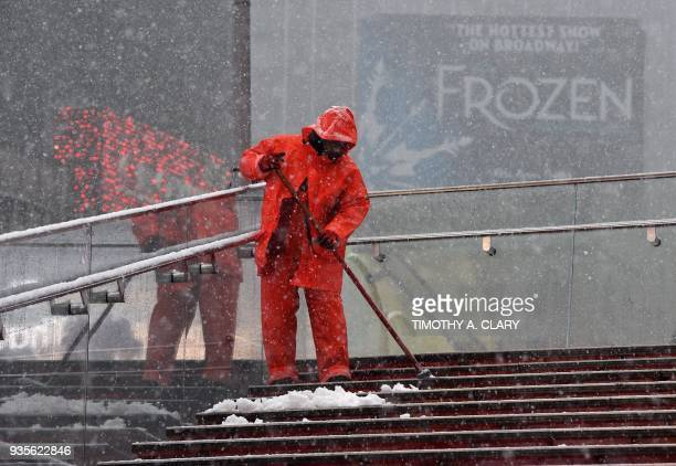 Workers clean steps at Times Square in New York on March 21 as the fourth nor'easter in a month hits the tristate area on the first full day of...
