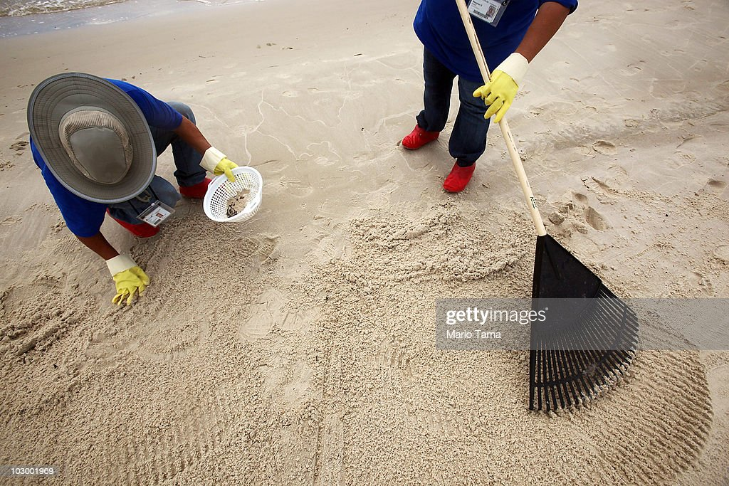 Workers clean tarballs from a beach July 20, 2010 in Waveland, Mississippi. According to reports, scientists are concerned that oil is leaking from the BP well cap could possibly make the sea bed unstable, causing the well to collapse.