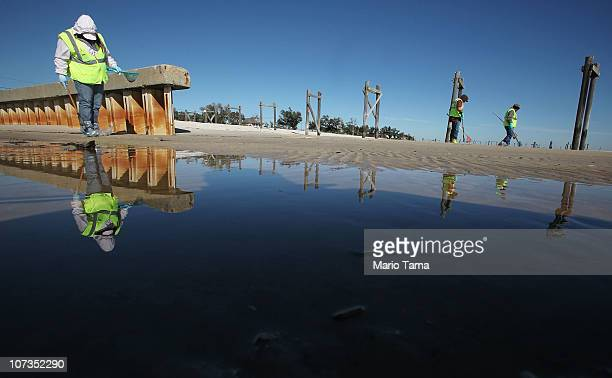 Workers clean tarballs from the BP oil spill on Waveland beach December 6 2010 in Waveland Mississippi Nearly eight months after the spill tarballs...