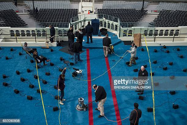 TOPSHOT Workers clean the carpet on the Inauguration platform in preparation for tomorrow's Inauguration on Capitol Hill on January 19 2017 in...