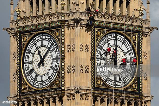 Workers clean the Eastfacing clock face of the Elizabeth Tower of the Houses of Parliament on August 19 2014 in London England Workers are cleaning...