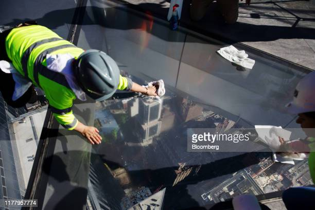 Workers clean the glass floor of the Edge observation deck at 30 Hudson Yards during a media preview event in New York US on Thursday Oct 24 2019...
