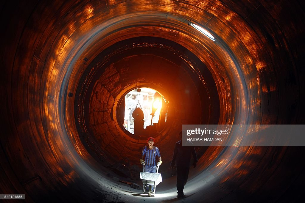 Workers clean the inside of a kiln at the Kufa cement plant