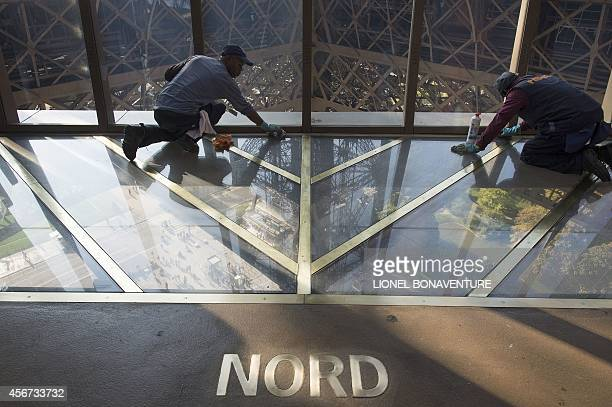 Workers clean the new glass floor at the Eiffel Tower in Paris on October 3, 2014. The Eiffel Tower is inaugurating a new glass floor on October 6...