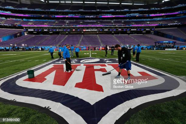 Workers clean the NFL logo at midfield at US Bank Stadium in Minneapolis MN during the leadup to Super Bowl LII where the New England Patriots will...