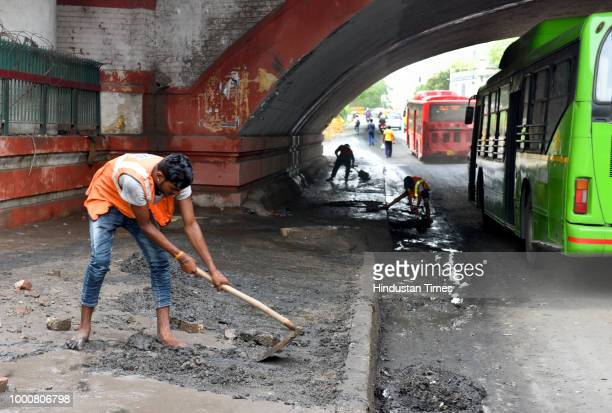 PWD workers clean the road at Minto Bridge underpass which saw neckdeep waterlogging following heavy rains on Monday in New Delhi India on Tuesday...