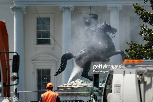Workers clean the statue of Andrew Jackson in Lafayette Square the day after protesters tried to pull down the statue of the former president near...
