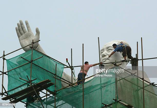 Workers clean the statue of former Chinese leader Mao Zedong to prepare for the upcoming National Day Holiday on September 22 2008 in Chengdu of...