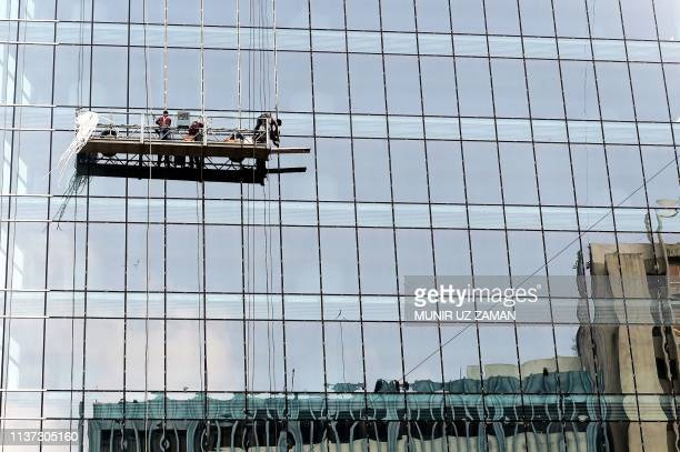 Workers clean the windows and the facade of a highrise building in Dhaka on April 15 2019