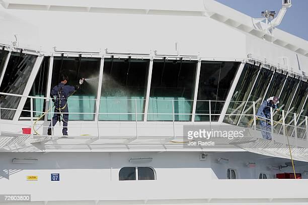Workers clean the windows as passengers disembark from the Carnival Liberty Cruise ship at Port Everglades on November 19 2006 in Fort Lauderdale...