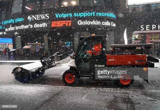Workers clean Times Square in New York March 21 as the fourth nor'easter in a month hits the tristate area on the first full day of spring Winter...