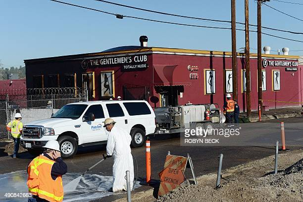 Workers clean up after an above ground oil pipeline ruptured causing some 10000 gallons of crude oil to spill into the streets of Los Angeles on May...