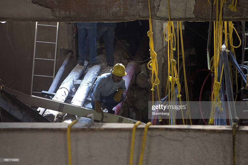 Workers clean up debris at the Petroleos Mexicanos headquarters building in Mexico City, Mexico, on Tuesday, Feb. 5, 2013. Mexican authorities said a buildup of gas led to the blast last week that killed 37 people at Petroleos Mexicanos's headquarters, the first official attempt to explain the nation's deadliest explosion since 2006. Photographer: Susana Gonzalez/Bloomberg via Getty Images