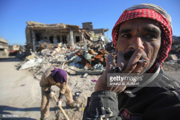 TOPSHOT Workers clean up debris from a street in Mosul's Old City on January 8 six months after Iraqi forces seized the country's second city from...