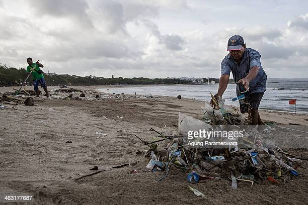 Workers clean up piles of the debris brought in by strong waves at Kuta Beach on January 17 2014 in Kuta Indonesia The sight of trash washed up on...