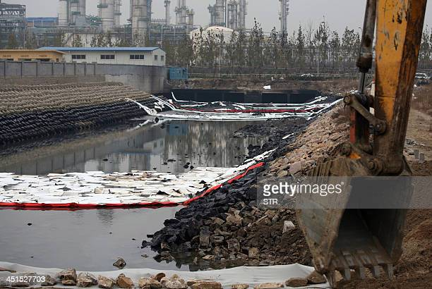 Workers clean up the oil slick on the river of Jiaozhou Bay after an oil pipeline exploded ripping roads apart turning cars over and sending thick...