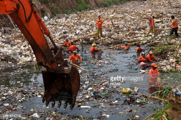 TOPSHOT Workers clean up tons of waste from Pete river in Bekasi West Java on November 12 2019