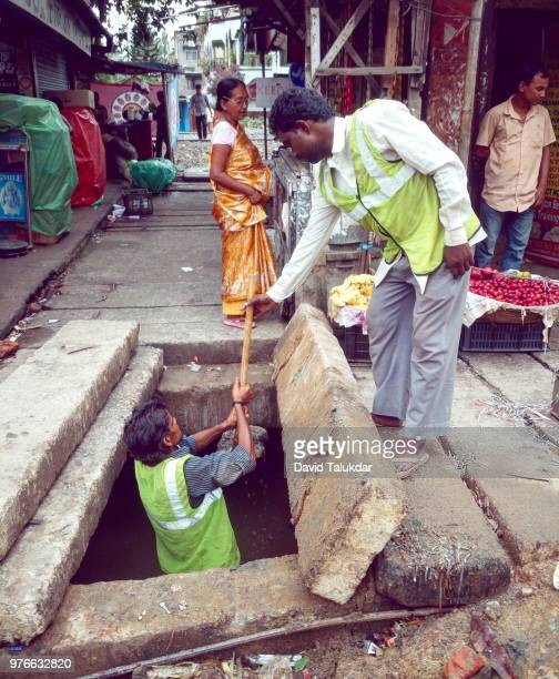 workers cleaning drains - drain cleaner stock photos and pictures