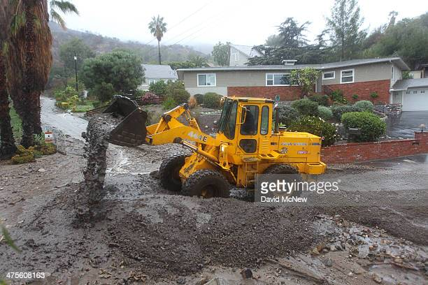 Workers clear a path through ash rocks and mud that have flowed onto a street below the Colby Fire burn area as a storm brings rain in the midst of...