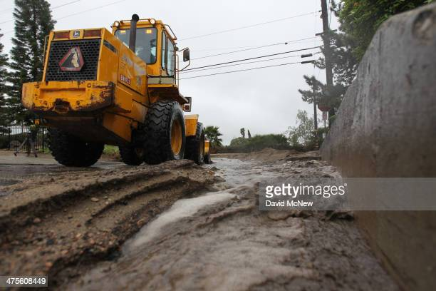 Workers clear ash rocks and mud that have flowed onto a street below the Colby Fire burn area as a storm brings rain in the midst of record drought...
