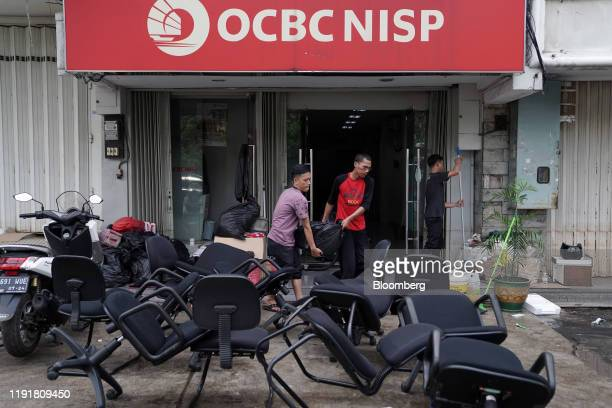 Workers clear debris at a PT Bank OCBC NISP Tbk branch following flooding in Jakarta Indonesia on Saturday Jan 4 2020 At least 53 people have died...