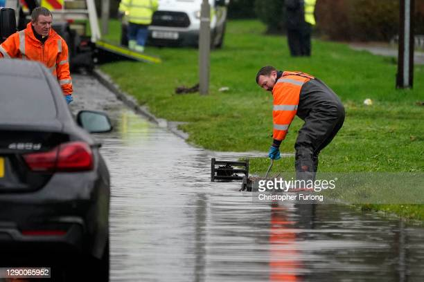 Workers clear drains to help reduce flood water in West Derby as localised flooding causes disruption on December 08, 2020 in Liverpool, England....